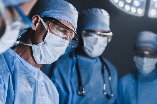 Concentrated surgeons operating patient in operating theatre. Healthcare workers concept.