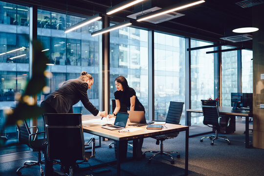 Confident male and female architects talking to each other brainstorming and cooperate on project in office interior, intelligent business partners preparing finance report communicating and analyzing
