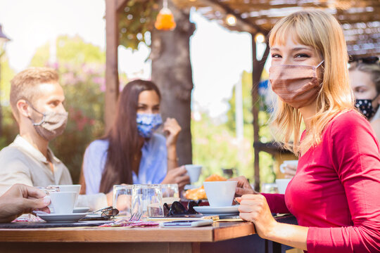 Happy young woman wearing face mask smiling at the camera at the restaurant cafè. Group of friends drinking coffee sitting at the bar. New normal concept.