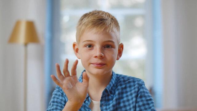 Happy cute little vlogger waving hand saying hello hi looking at camera talking to webcam