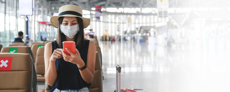 New normal travel of traveler asian woman with mask using mobile phone in airport Thailand