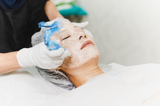 Woman having stimulating facial treatment at professional clinic.