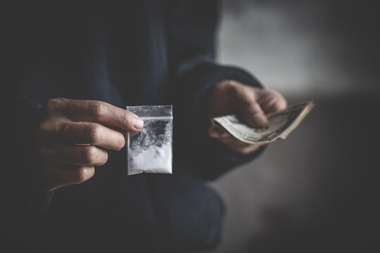 close up of addict with money buying dose, Purchase, possession and sale of drugs is punishable by law. drug trafficking,  addiction and sale concept.