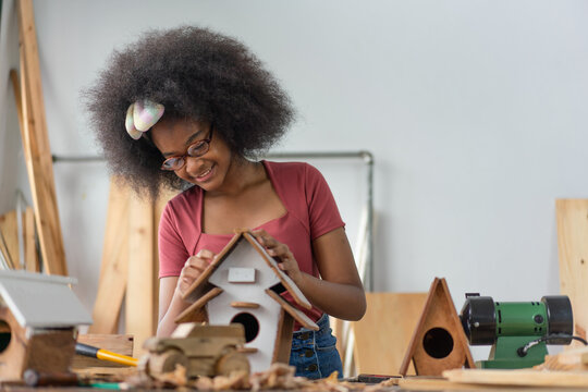 African American young girl craftswoman making wooden bird house at workshop