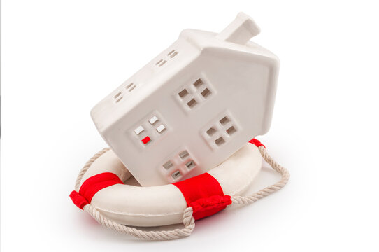 Property insurance, debt relief loan and mortgage assistance program due to covid19 emergency concept with photograph of house in lifebuoy isolated on white background with clipping path cut out