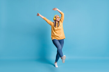 Photo sur Plexiglas Magasin de musique Full body size photo of attractive careless old dancer lady listen music earphones hands waving above head walking street wear sunglass yellow jumper jeans vivid blue color background