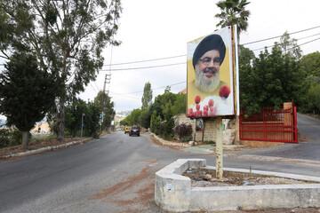 Cars drive near a poster depicting Lebanon's Hezbollah leader Sayyed Hassan Nasrallah at the entrance of the village of Ain Qana