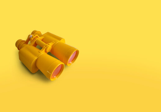 Yellow binoculars isolated on yellow background with copy space