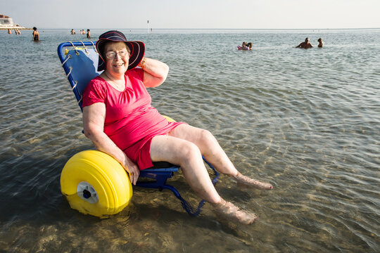 disabled senior lady on a special wheelchair in the sea water