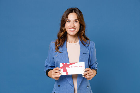 Smiling pretty beautiful attractive young brunette woman 20s in basic casual jacket standing holding in hand gift certificate looking camera isolated on bright blue colour background studio portrait.