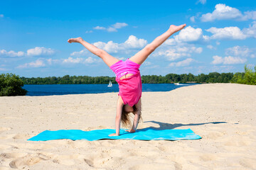 Little girl is engaged in gymnastics on the beach on a sunny day. Sports, vacation vacations. Active lifestyle.