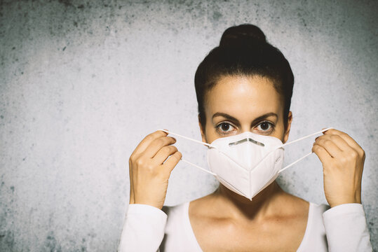 Woman putting on a medical mask to avoid contagious viruses.