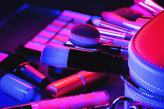 Cosmetic bag, makeup brushes, eyeshadows palette, lipstick and high heels shoes on the flat lay table background in the neon lights.