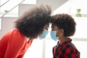 Mother and son wearing face mask looking at each other at home