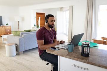 Man wearing headphones using laptop at home