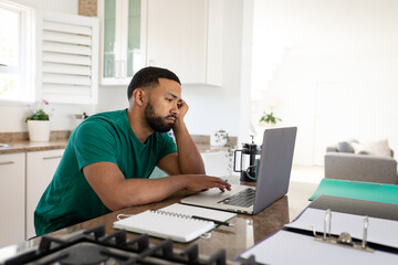 Tired man using laptop in the kitchen at home