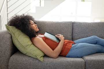 Woman with book sleeping on the couch at home