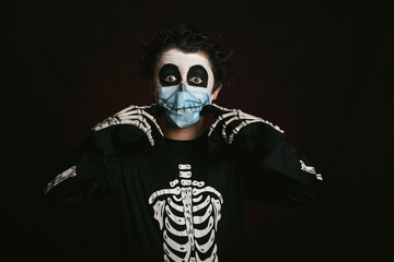 Happy Halloween,kid with medical mask in a skeleton costume making smile