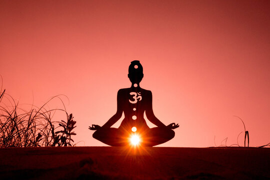 Silhouette of a person doing yoga with the root chakra symbol