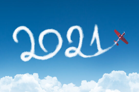 Happy New year 2021 concept on the background below cloudscape. Drawing by passenger airplane white vapor contrail in sky.