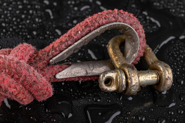 A wet shackle and a gray rope with a sailing knot. Accessories for sailors to operate boats covered with water drops.