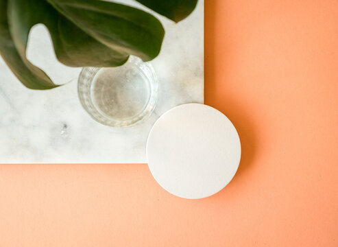 Mock up of a round coaster on a marble board with a glass