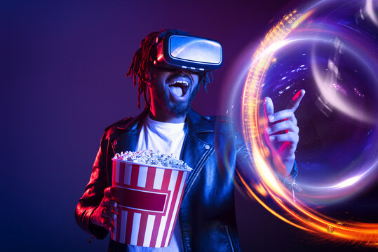 Man with VR glasses and popcorn watches a 3D film