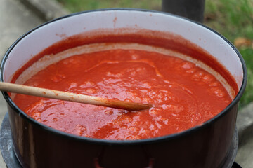 Close up on big pot with wooden spoon stirring hot ketchup or tomato sauce or soup while cooking outdoor - homemade with traditional recipe organic food concept