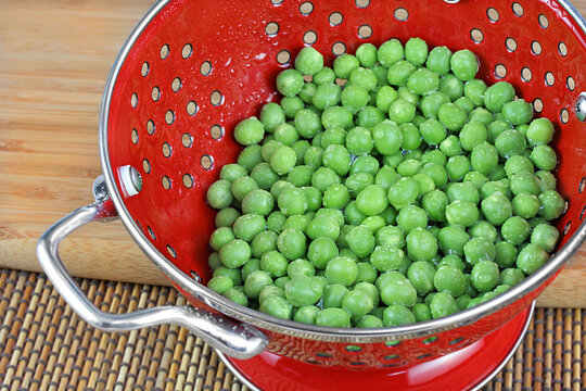 Fresh, washed peas in a red colandar