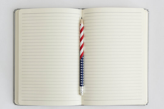 Open blank notebook with a stars and stripes pencil