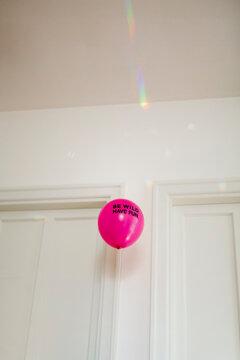 Fluo magenta balloon sayin Be wild. Have fun. flies inside bright room