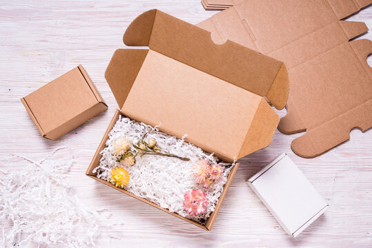 Brown cardboard box with paper filler on wooded desk, top view