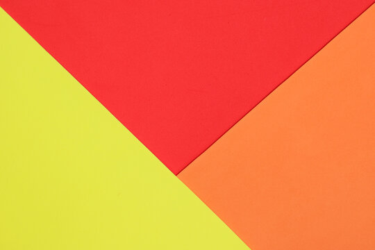 An abstract geometric textured background of yellow, red and orange created with overlapping foam craft paper
