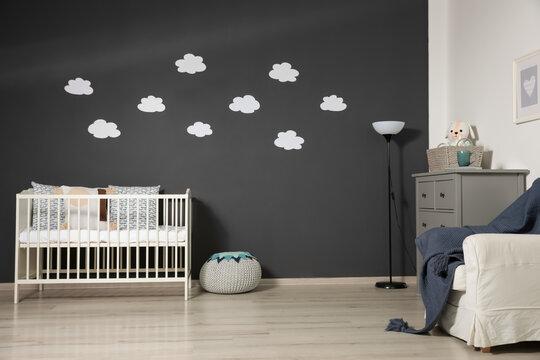 Cute baby room interior with modern crib near decorative clouds on dark wall