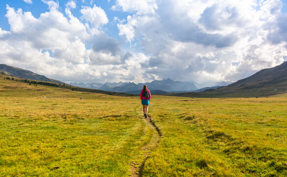 Woman walking in the road fronting a mountains