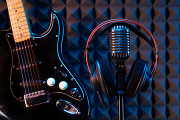 Studio microphone with professional headphones and black electric guitar