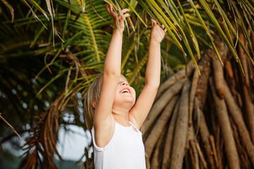 Portrait of happy little girl with palm leaf. Summer vacations concept, tropical vibes. Kid smiling