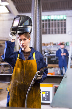 Portrait of female welder in factory workshop. High quality photo