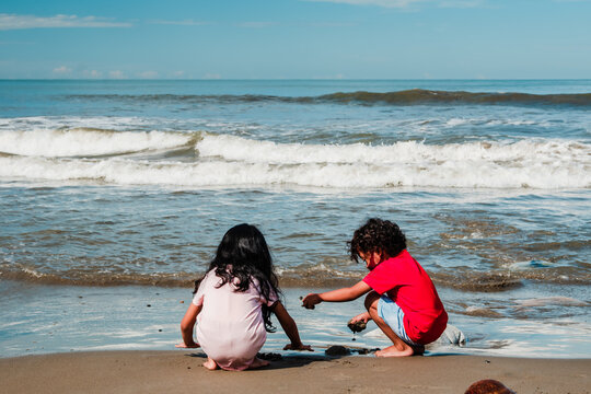 Asian girl and boy are playing water by the sea. Kids in nature or outdoor. Cute children enjoying the beach.