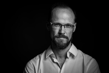 Black and white portrait of man in glasses looking concentrated in camera