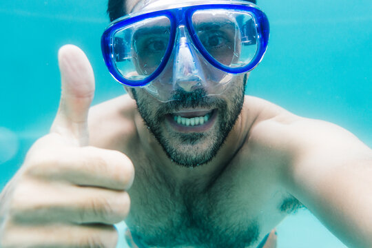Underwater selfie of smiling man in diving mask showing thumb up
