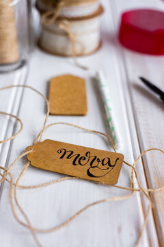 """xmas tag with handwritten word """"""""merry"""""""" in ink lettering"""