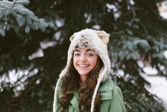 An adorable preteen girl with braces posing for a picture in the snow