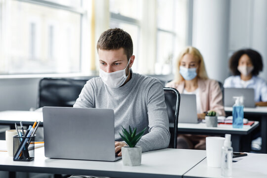Coworking office and safe work during coronavirus epidemic. Young man with face mask back at work in office after lockdown and looks at laptop
