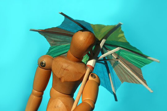 Wooden mannequin with colored beach umbrella. Close up of the puppet holding the opened umbrella in front of turquoise background with copy space.