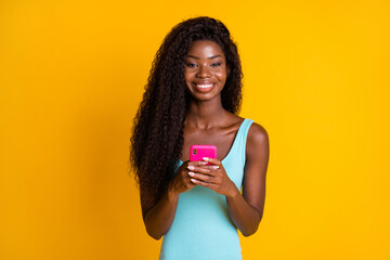 Photo portrait of happy african american woman holding pink phone in two hands smiling wearing blue...