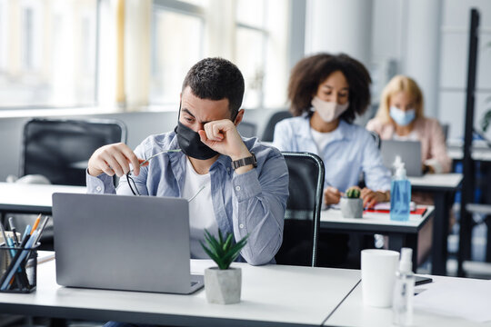 Tired and overworked. Focus on man in protective mask rubs eyes with hand, behind sit female colleagues at workplaces with laptops and antiseptics