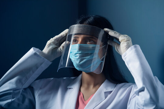 Female doctor wearing a face shield to protect herself from coronavirus