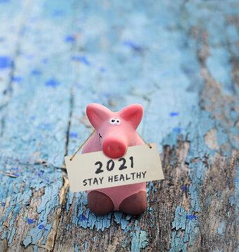 Kleines rosa Glücksschwein, mit Tafel und Aufschrift: 2021 Stay Healthy, auf altem, blauen Holz.