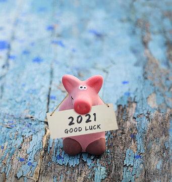 Kleines rosa Glücksschwein, mit Tafel und Aufschrift: 2021 Godd Luck, auf altem, blauen Holz.